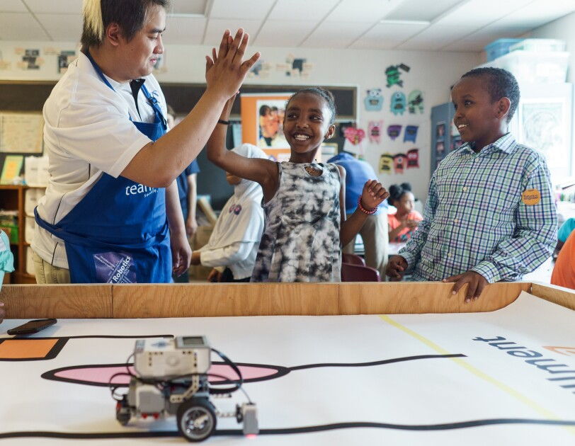 A girl smiles while getting a high five in a classroom. In the foreground, a robotic toy moves along a hand-drawn line.