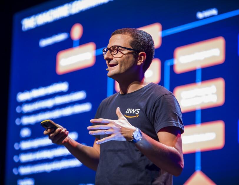 Przemawiający mężczyzna z ekranem prezentacji w tle