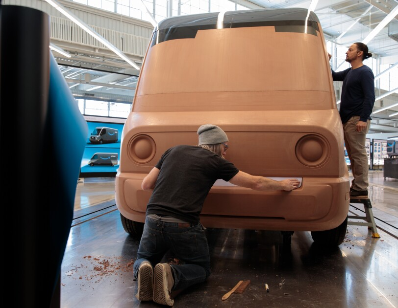 Two men work on a large clay model of a delivery van.