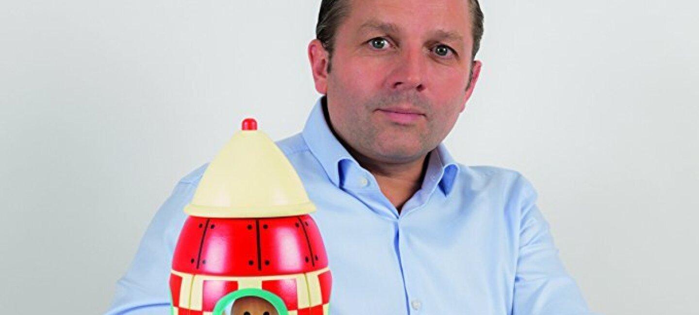 Le fondateur de Janod se tient devant l'un de ses jouets en bois qui représente une fusée à carreaux rouges et blancs avec un dessin naïf de personnage regardant par un hublot