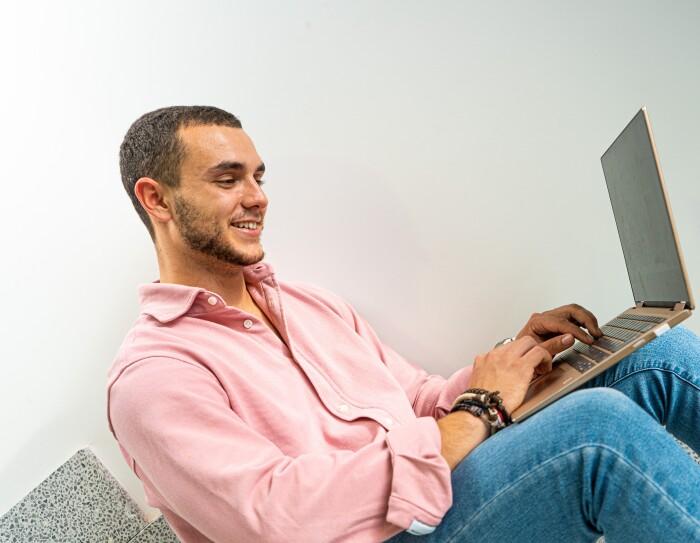 Jordi Cascant  sentado en unas escaleras y trabajando con el ordenador en las piernas. Lleva unos jeans, una camisa rosa, unas pulseras en la mano derecha y un relo en la mano izquierda. Tiene el pelo negro y barba de dos días.