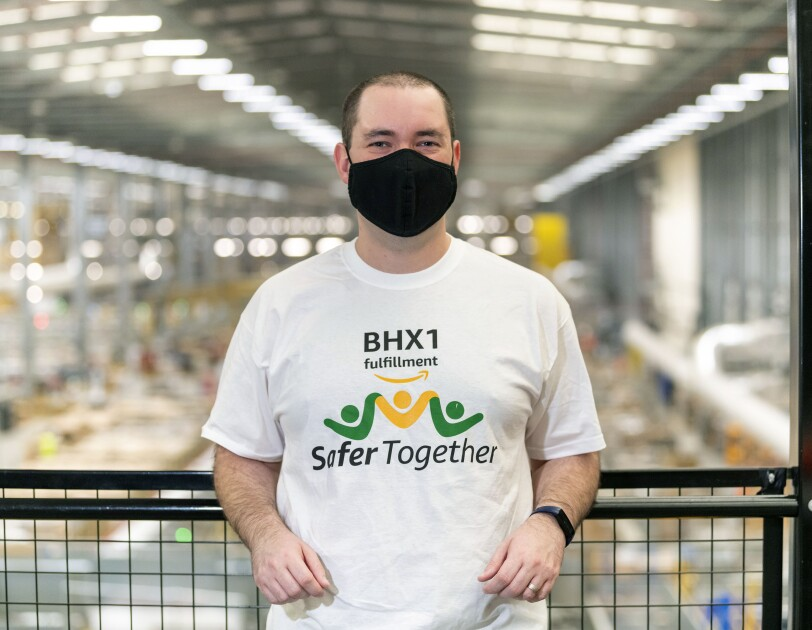 Ben Farbrother, Finance Assistant at Amazon's fulfilment centre in Rugeley, pictured stood on a mezzanine with the shop-floor blurred in the background.