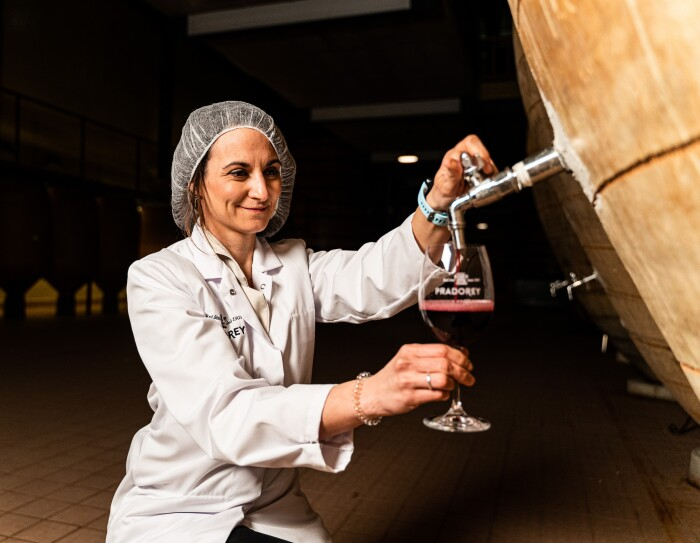 Pilar Moretón, responsable de I+D+I e de Pradorey. Origen es el vino de Pradorey más vendido en Amazon. Es un vino que madura en tinajas de barro. Abirendo una tinaja de barro para poner vino en una copa que ella sujeta. Pilar está de rodillas y va vestida con una bata blanca y un gorro de protección. Llev aun reloj de color azul en la mano izquierda y una goma para el pelo transparente en la muñera derecha.