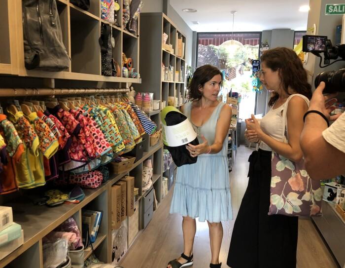 Irene está en una tienda donde se vende su producto. Está conversando con la propietaria de la tienda que tiene en la mano el bolso Andone Dynamic Walks. Irene tiene el pelo largo y viste una camiseta blanca sin mangas y una falda hasta los pies negra.