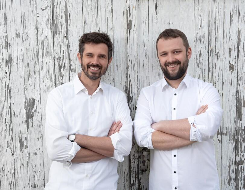 Zwei Männer mit dunklen Haaren und weißen Hemden stehen vor einer Wand und lachen in die Kamera.