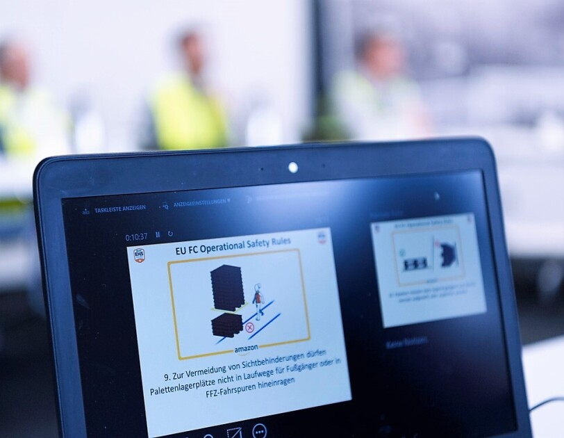 """Auf einem aufgeklappten Laptop-Bildschirm ist zu lesen: """"Zur Vermeidung von Sichtbehinderungen dürfen Palettenlagerplätze nicht in Laufwege für Fußgänger oder in FFZ-Fahrspuren hineinragen."""" Dazu sieht mal eine Illustrationen, die das richtige/falsche Abstellen darstellt."""