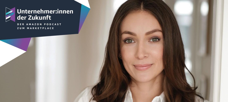 Eine Frau mit braunen langen Haaren und einer weißen Bluse lächelt in die Kamera.