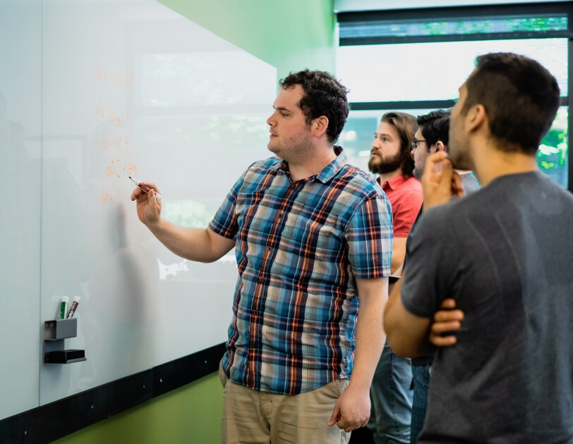 A group of people work at a whiteboard.