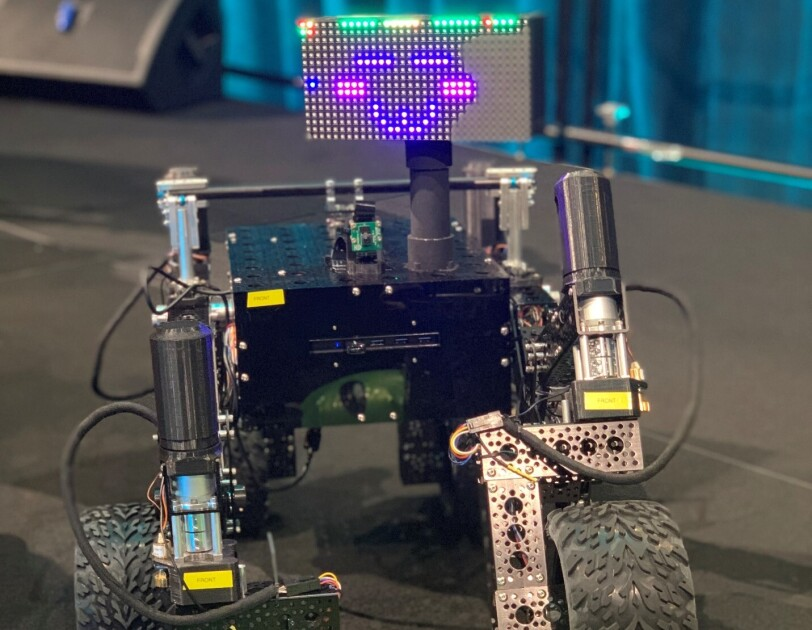 A small robot with wheel feet and an LED face