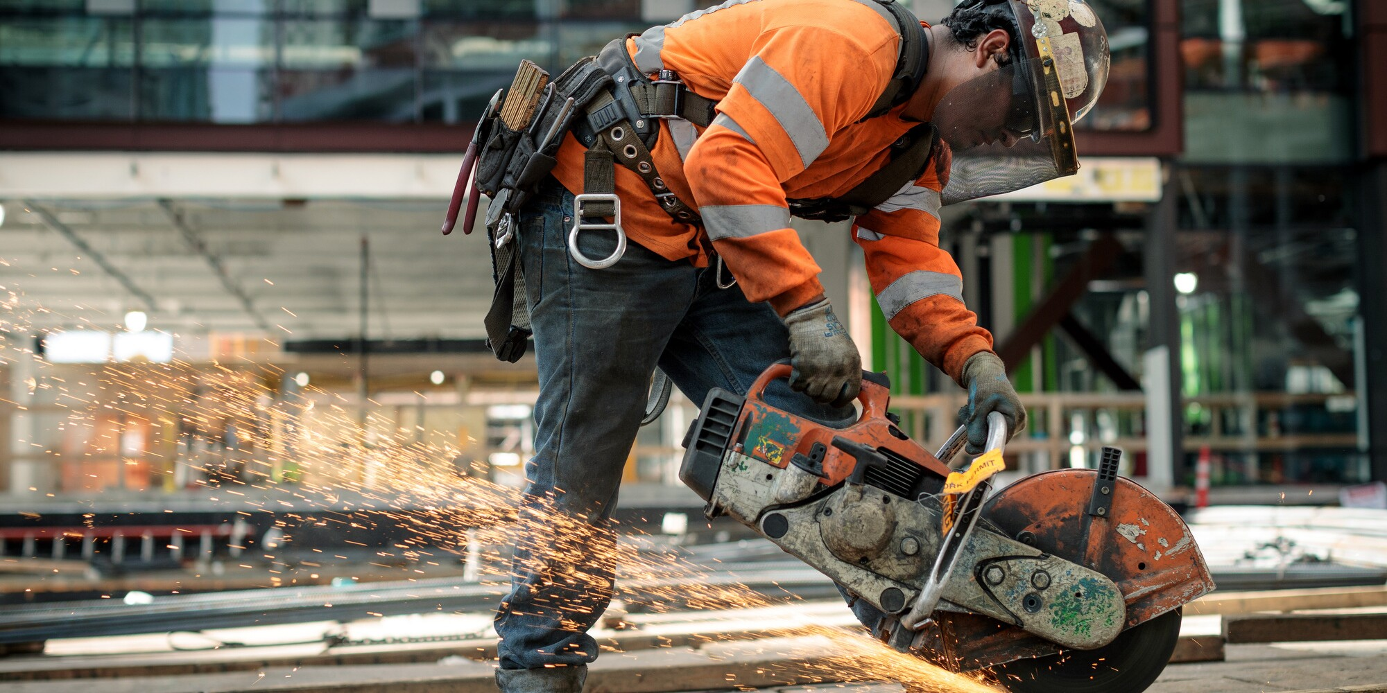 A man in construction helmet and orange safety jacket is photographed at a construction site on Amazon's campus in Seattle, WA. he is using a saw to cut through tubing.