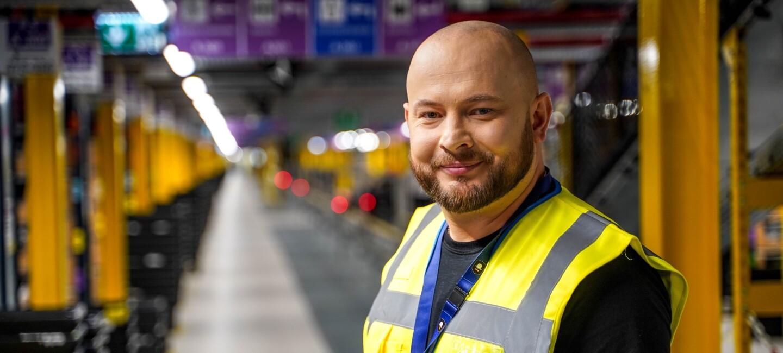 Pracownik Amazon stoi w centrum logistyki i uśmiecha się.