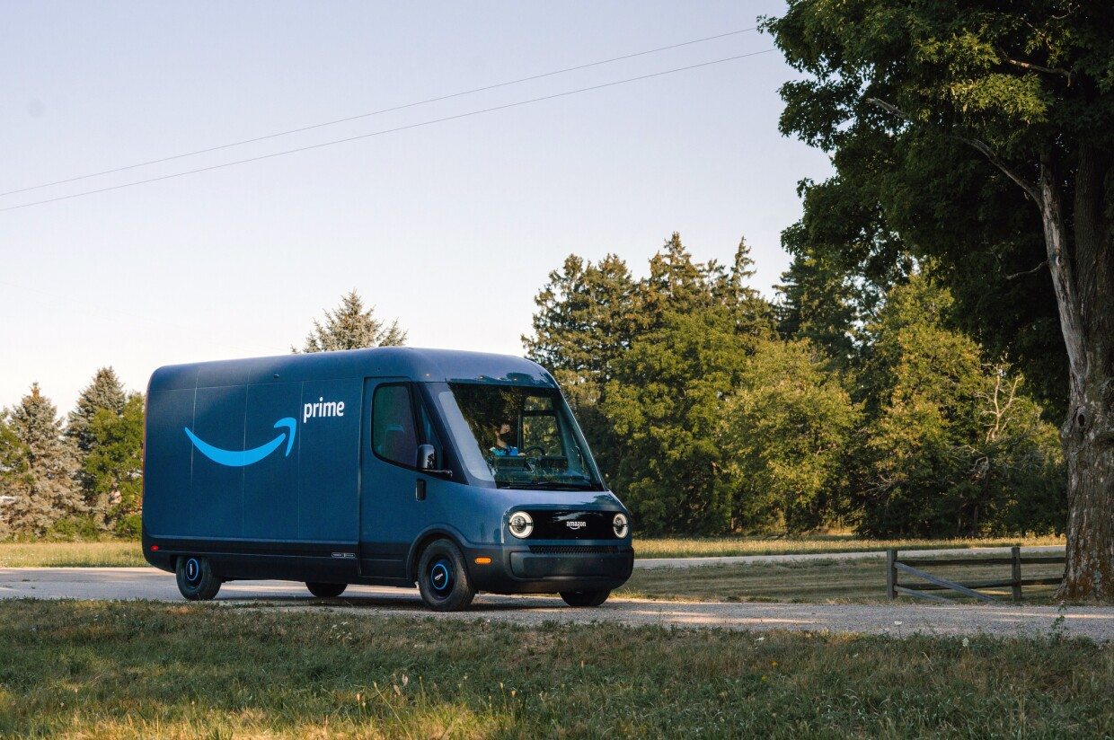 A blue Amazon electric vehicle driving through a country road.