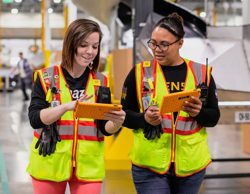 Two women in a warehouse space. Each of them holds a tablet.