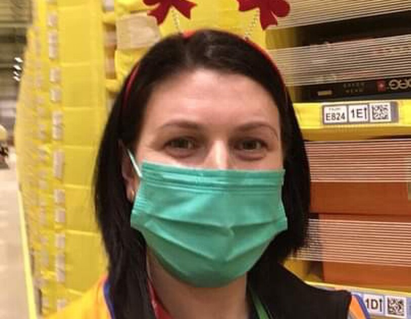 Diana Campean, Associate at Amazon's fulfilment centre in Dunstable pictured in front of lots of yellow pods full of inventory. Diana is wearing a green face mask and a festive headband with two snowmen.