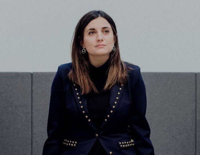 Nuria Pastor es licenciada en Psicología y MSc en Neurociencias y CEO de Humanitcare. Con una americana con tachuelas doradas y un jersey de cuello alto debajo. Está mirando al horizonte y tiene el pelo castaño gris por el hombro.