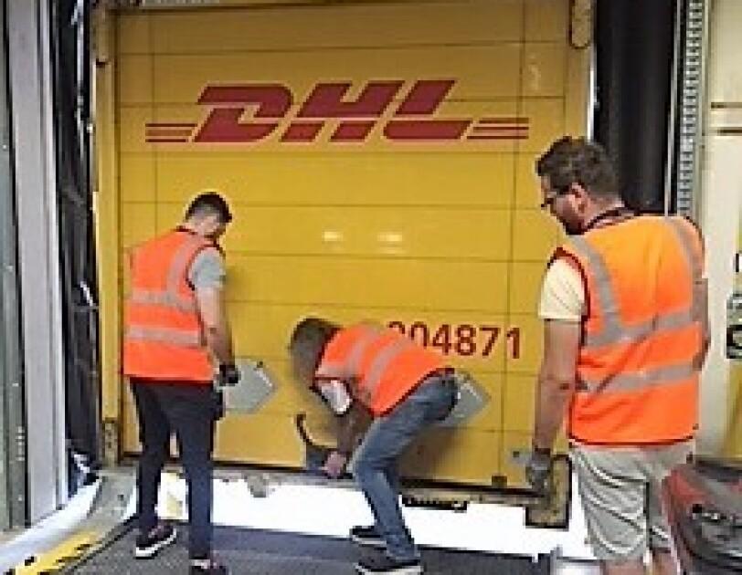 3 Versandmitarbeiter mit orangenen Warnweste sind vor einer Laderampe des Logistikzentrum zu sehen. Die Mitarbeiterin in der Mitte schließt gerade die Versandklappe des Lkws.