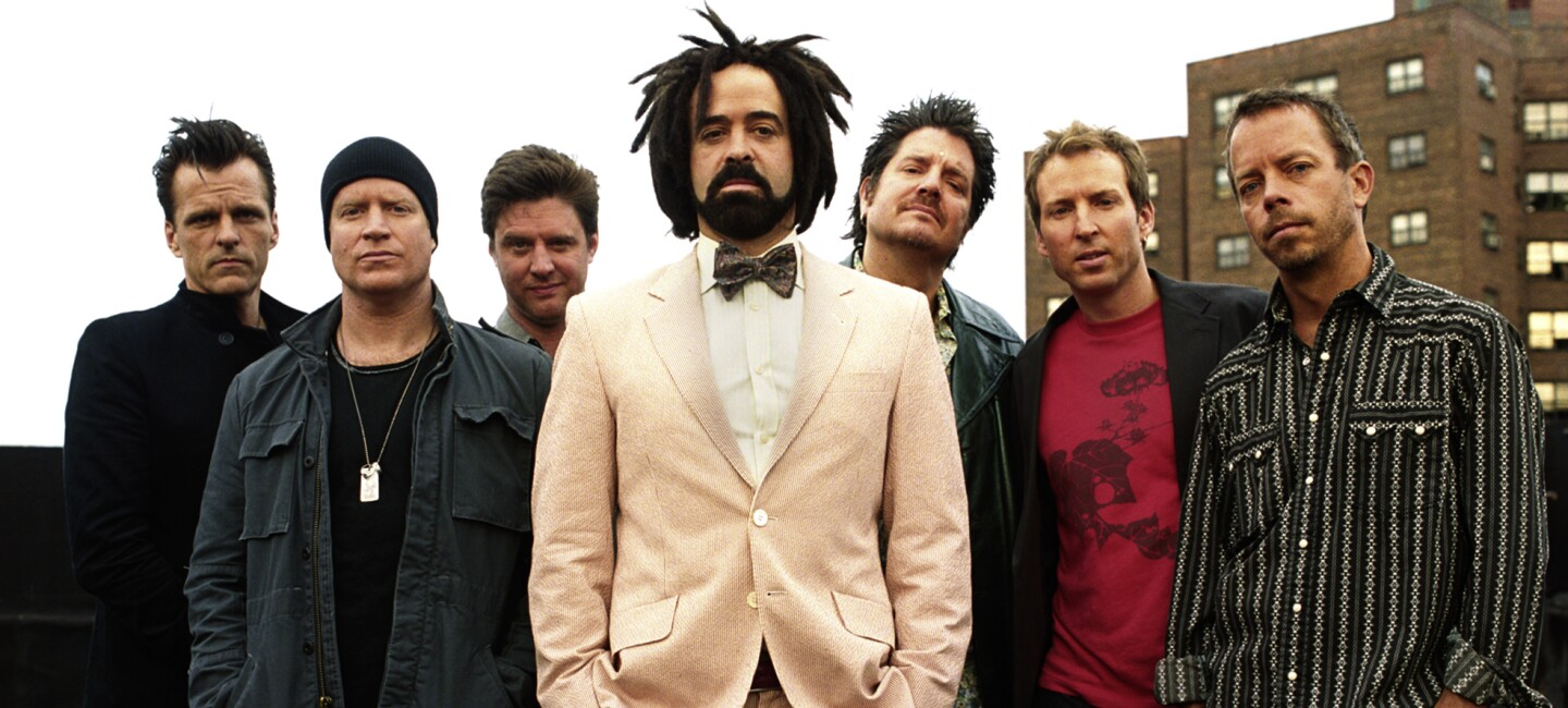 The Counting Crows band, six men stand together wearing casual clothing. In front of them, Adam Duritz stands in a cream suit with bow tie and tennis shoes.