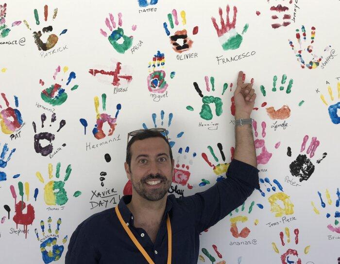 Ritratto a mezzo busto di Francesco Magini, responsabile del Kindle Store per l'Europa. L'uomo indossa gli occhiali da sole sulla testa e con il braccio sinistro tenuto in alto su di sè indica il muro alle sue spalle, ricoperto di impronte colorate di mani.