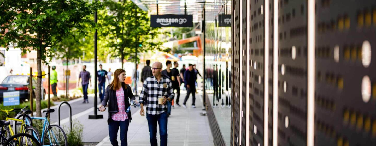 Amazon employees walk on the sidewalk past Amazon Go flagship store in Seattle, Washington