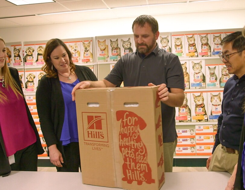 Three women and two men stand around a carboard container decorated with the Hill's Pet Nutrition logo. Various dogs and cats on Hill's packaging are in the background of the image.