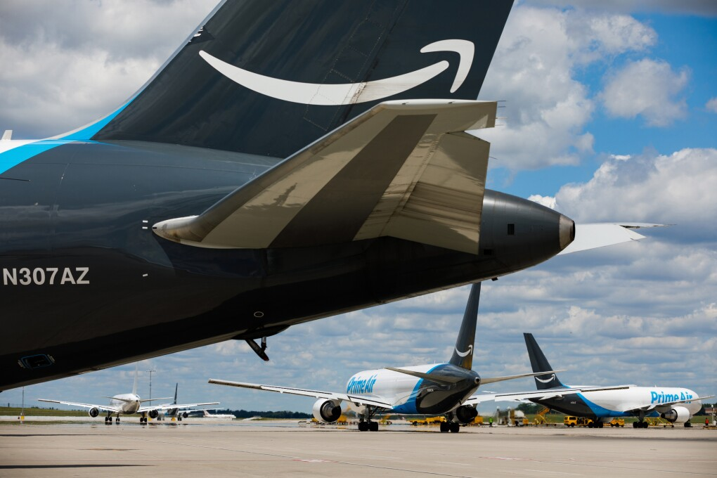 "The tail of a plane with the Amazon smile logo. Two other planes labeled ""Prime Air"" are visible in the background."