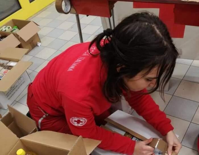 Volontaria della Croce Rossa inginocchiata per terra mentre chiude un pacco di generi alimentari.