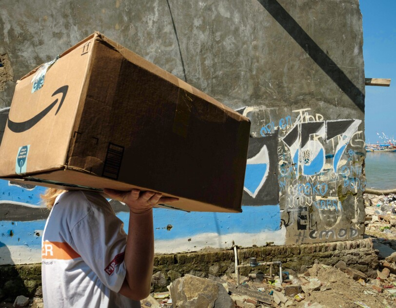 A person carries an Amazon box through a waterfront strewn with debris.