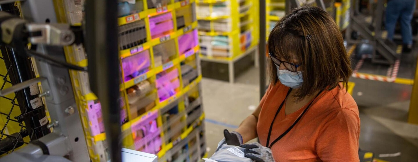 A woman wearing gloves and a face mask works at an Amazon fulfillment center.