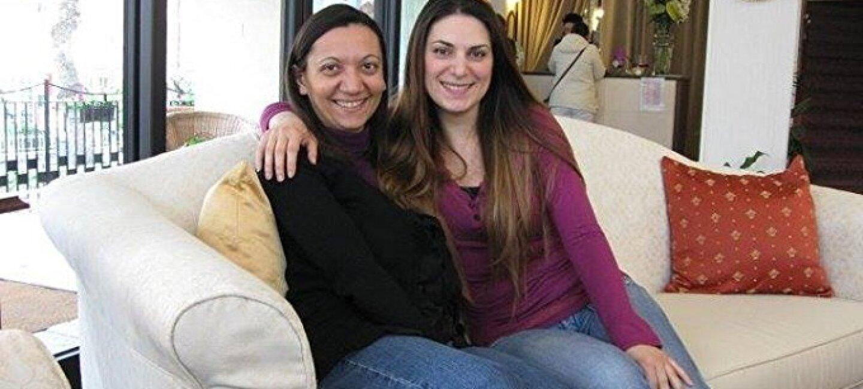 Angela Contini e Patrizia Zinni siedono su un divano bianco nella loro caso. Sono le autrici che si celano dietro l'alias di Katherine Keller, nota ai lettori come l'autrice di The Shadows Saga, una trilogia di romanzi fantasy di grande successo disponibile sul Kindle Store di Amazon.it.