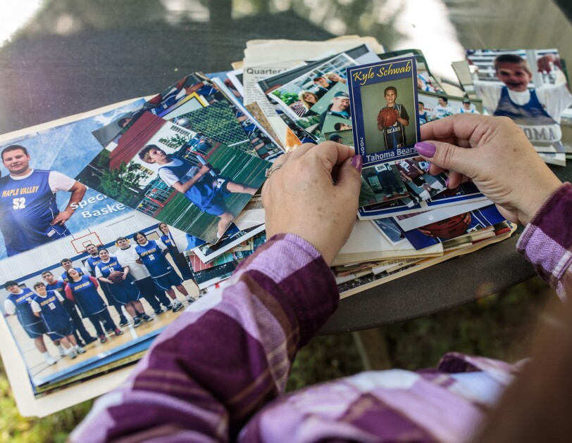 A woman sits and holds a photo. A folder of photos and mementos is open on her lap.