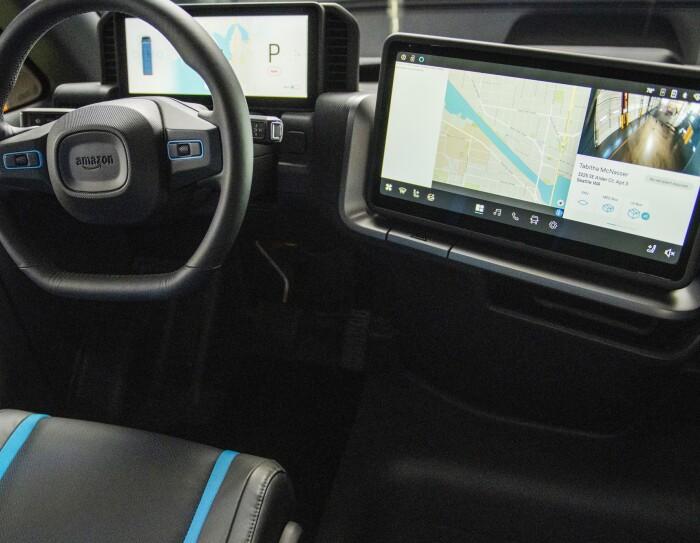 Un dettaglio della postazione del conducente del furgone elettrico Rivian. Accanto al volante, a destra, un grande schermo LCD con il navigatore.