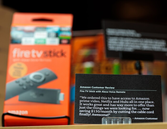 "A black ""customer review card"" inside the Amazon 4-star store in New York City. The review is for an Amazon Fire TV stick with Alexa Voice Remote."