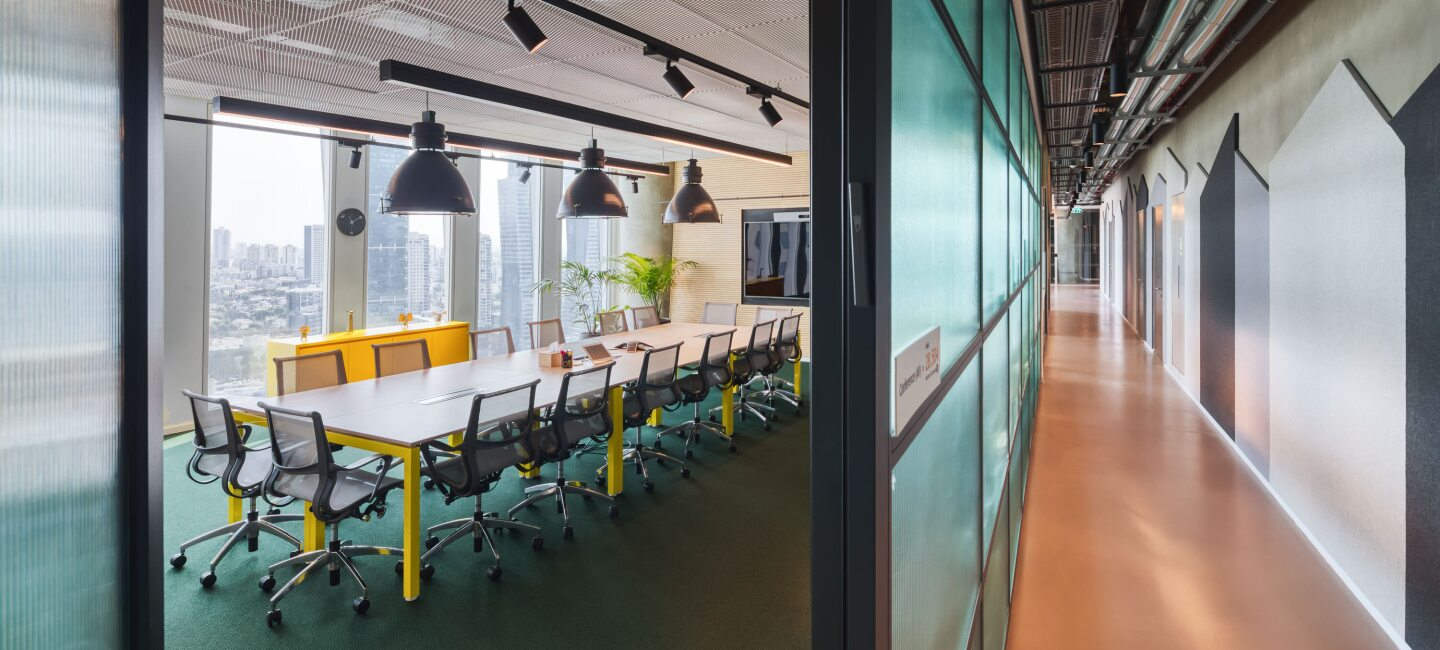 AWS Office in Tel Aviv. left hand side is a meeting office with a long meeting table and right hand side is the hallway.