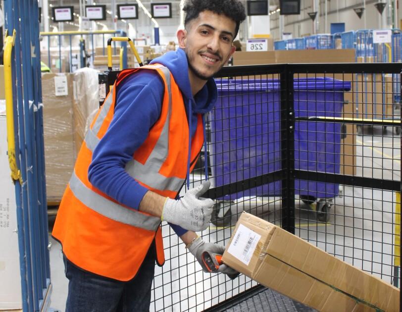 Ein Mitarbeiter mit dunklem, gelocktem Haar legt gerade ein Paket auf einen Gitterrollwagen. Er trägt eine gelbe Sicherheitsweste und blickt lächelnd in die Kamera.