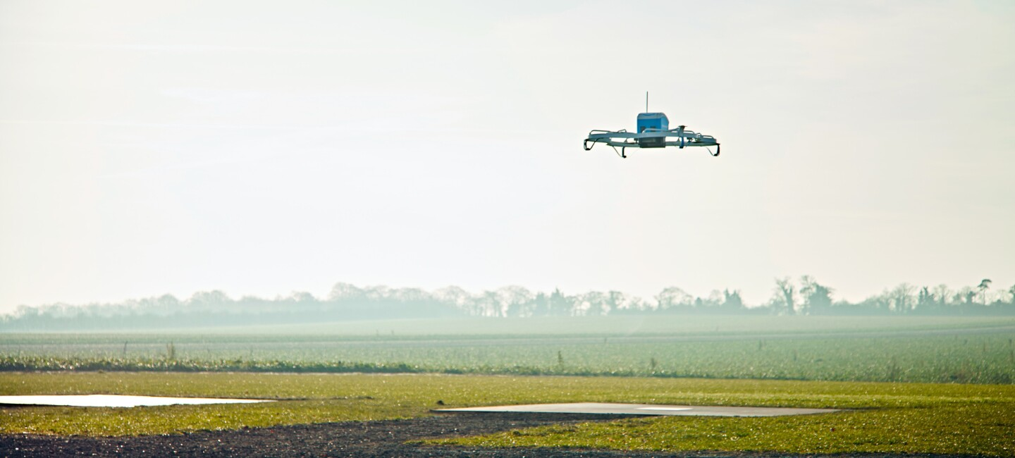 An Amazon Prime Air drone hovers over a field near the Amazon Prime Air test facility in the United Kingdom