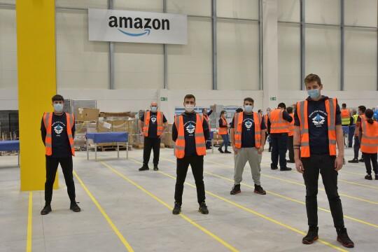 Un gruppo di dipendenti Amazon posa in occasione dell'apertura del magazzino di Genova. 5 ragazzi giovani guardano verso la camera.