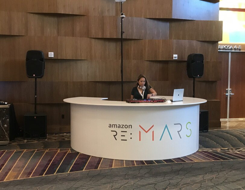 "A DJ booth branded with ""re:MARS"" with a female DJ mixing beats for attendees."
