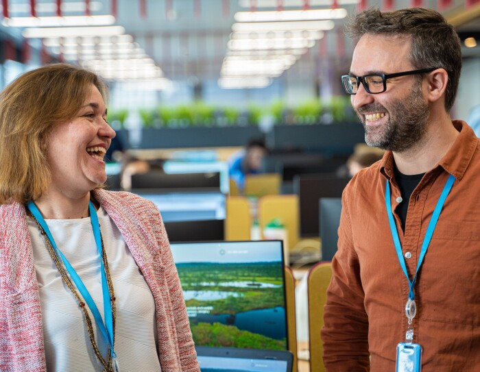Marta Fernández y Daniel Méndez son Content Program Manager de Alexa. Los dos se miran y sonríen. Marta lleva una camiseta blanca y una chaqueta rosa. Tiene el pelo corto, media melena y es rubia. Daniel lleva una camiseta negra y una camisa marrón.