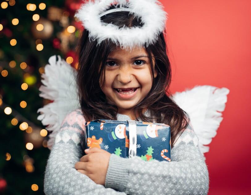 Ein dunkelhaariges Mädchen mit weißen Engelsflügeln hält ein blaues Geschenk in den Armen und lächelt in die Kamera. Im Hintergrund sieht man einen geschmückten Weihnachtsbaum.