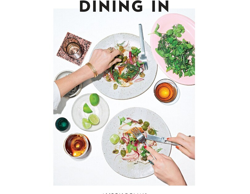 "cover of a cookbook, called ""Dining In"" shows a woman with fork and knife poised to pick up items from her dinner plate, while another arm reaches across the table to grab an olive. drinks, lime slices and other accoutrements are tastefully organized."