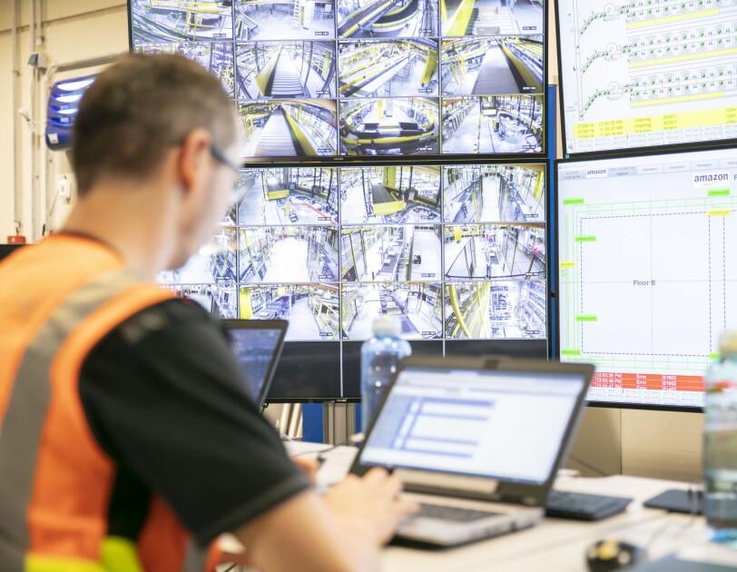 Ein Mitarbeiter in orange-farbenen Weste tippt an einem Laptop. Vor ihm sieht man auf großen Bildschirmen Technik und Förderbänder.