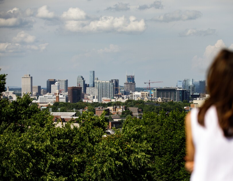 A distant view of the Nashville skyline with a woman in the foreground and trees in the middleground.