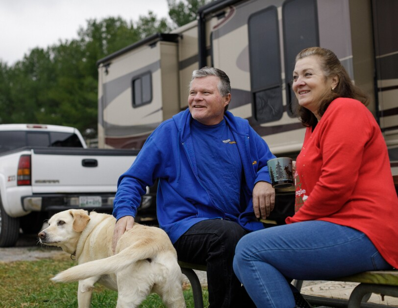 A dog, a man, and a woman photographed outside a motorhome.