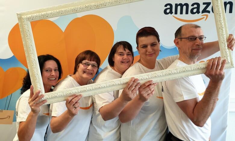 Eine Gruppe von Amazon Mitarbeitern in weißen T-Shirts mit Amazon Logo vor einer Fotowand