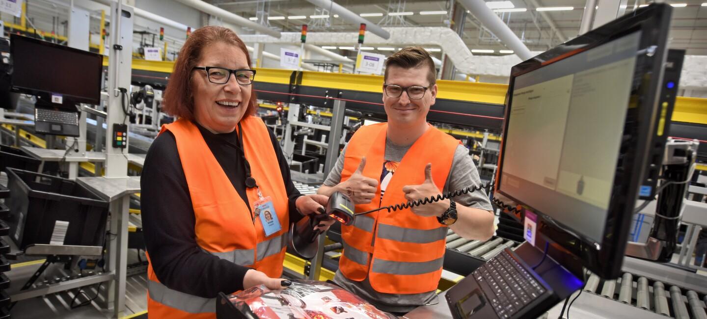 2 Amazon Mitarbeiter an einer Arbeitsstation: Links: eine Frau mit Brille und rötlichen Haaren; rechts: ein Mann mit braunen Haaren und Brillen; Beide tragen orangene Sicherheitswesten und lächeln in die Kamera.