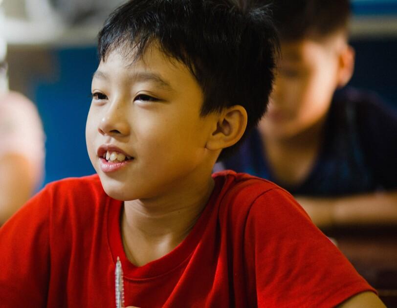 Ein asiatischer Junge im roten T-Shirt sitzt in der Schulbank. Im Hintergrund sieht man weitere Schulkinder, die am Unterricht teilnehmen.