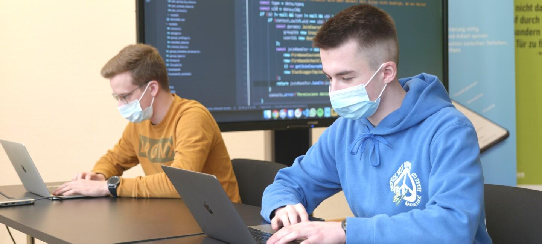 Zwei Jungen mit Masken sitzen an einem Tisch und schauen in ihre Laptops. Im Hintergrund ist eine Leinwand mit Computerbildschirm sichtbar.