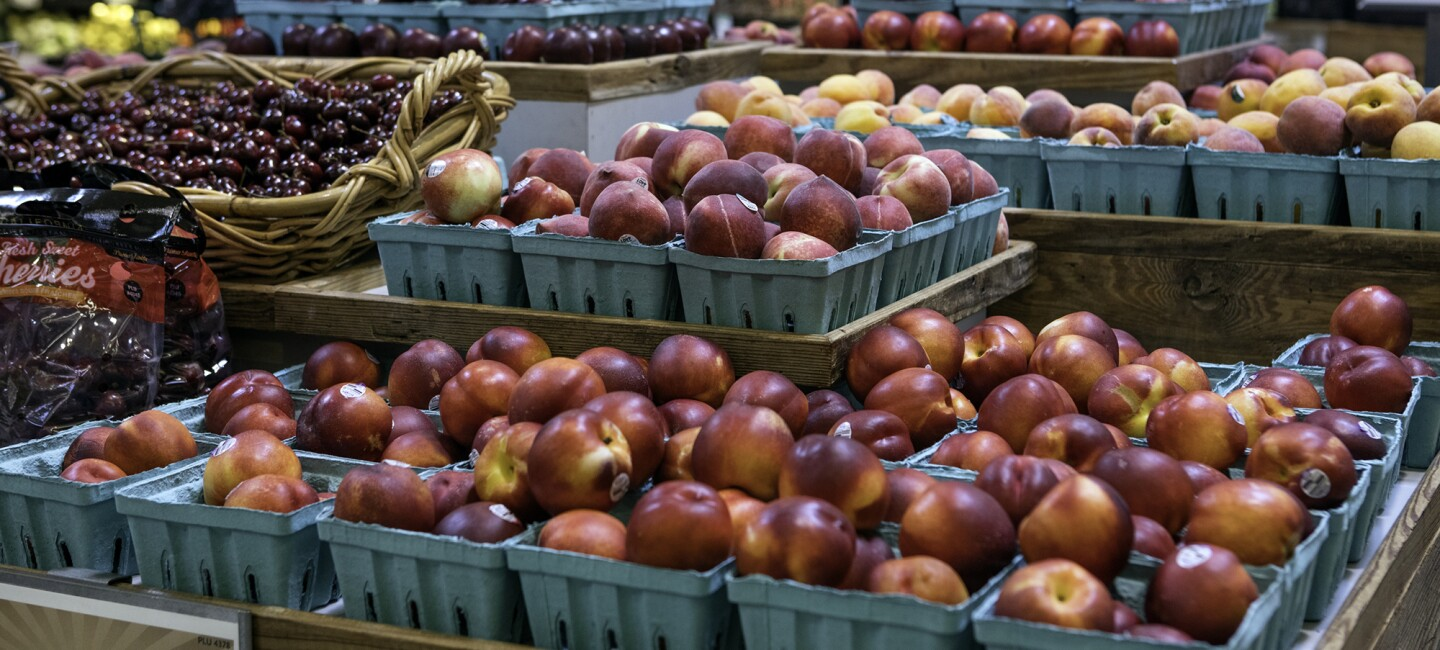 Produce displayed in a Whole Foods Market store - nectarines, cherries, and peaches are in the foreground, with a refrigerated juice display behind it.