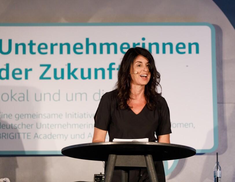 Brigitte Huber steht auf de Bühne am Rednerpult, sie hält eine Laudatio und verkündet die Gewinnerin