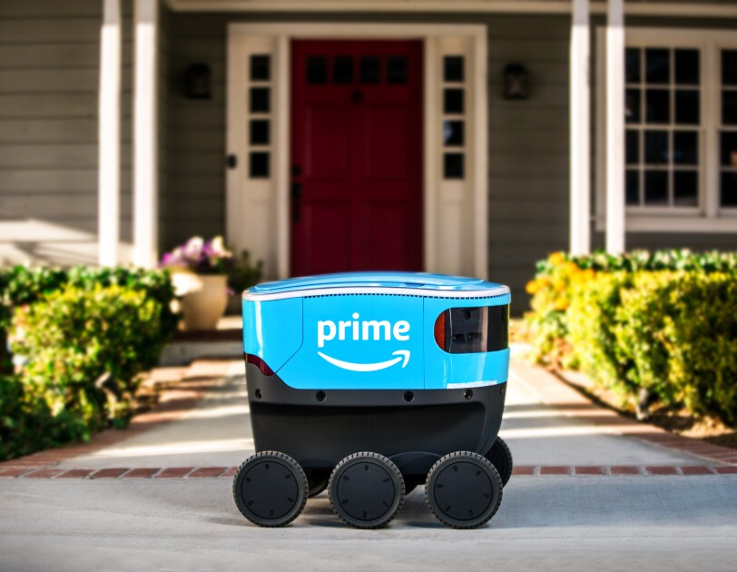 A small blue delivery bot with Amazon Prime branding sits on a walkway that leads to a house.